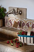 Chip wood basket of strawberries on side of stone sink; water running from wall-mounted taps above old, patterned wall tiles