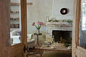 View through rustic double doors of simple coffee table in front of masonry fireplace, bouquet of lilies on bistro table and country-style armchair