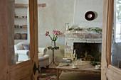 Blick durch rustikale Flügeltür auf einfachen Couchtisch vor gemauertem Kamin, Lilienstrauss auf Bistrotisch und Landhaus Sessel