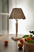 Apricots on table and in wicker basket in front of county-house-style table lamp