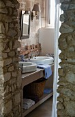 View past rustic stone wall of washstand with twin basin in bathroom