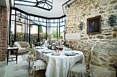 Rustikale Wand in hellem Essraum mit großem, gläsernen Erker; im Vordergrund ein langer, gedeckter Esstisch mit vergoldeten Barockstühlen und romantischen Hussen