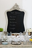 Chalkboard in ornamental frame behind collection of crystal vessels on rustic console table