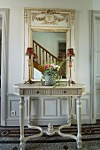 Grey console table below mirror with ornate frame reflecting staircase