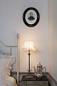 Oval portrait above nostalgic bedside lamp and silver coffee pot on bedside table