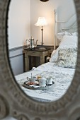 Corner of room with nostalgic bed, lit bedside lamp and breakfast tray reflected in mirror
