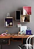 Verschiedene Boxen mit bemalten Innenflächen bieten auf kreative Art Stauraum im Arbeitszimmer
