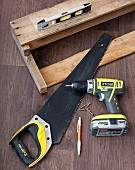 Saw and cordless drill next to home-made, wall-mounted shelf and spirit level