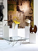 Chairs, ceramic pot and sculpture on pedestals and glass table in front of tapestry