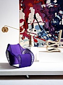 Designer chairs and lamp in front of tapestry