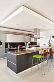 Gray, kitchen counter with colorful, upholstered bar stools in an open kitchen