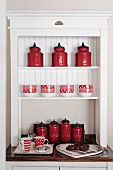 Red, retro style canisters in an white, open storage cabinet