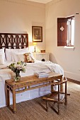 Moroccan-style bedroom with simple wooden table and rustic chair at foot of bed