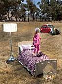 Girl bouncing on bed next to lit standard lamp in twilight meadow with old Beetle in background