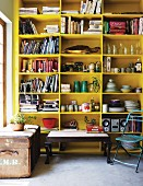 Coffee table next to vintage leather trunk in front of yellow-painted shelving holding crockery and books