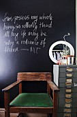 Holzstuhl mit grünem Sitzpolster und Büro Metall- Container im Vintagelook vor schwarzer Wandtafel