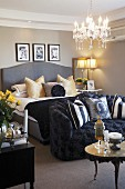 Traditional bedroom with grey double bed and black upholstered sofa at foot; soft scatter cushions create a cosy atmosphere