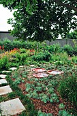 Garden with stone-flagged path & decorative dishes of water