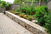 Raised bed edged by stone wall