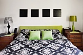Double bed with headboard upholstered in olive green below four square, monochrome black pictures