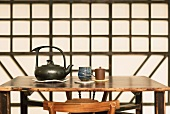 Ceramic teapot and teacups on Chinese-style wooden table: geometric wooden wall decoration in background