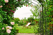 View of deckchair through archway covered in flowering roses