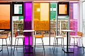 Tall tables and bar stools in front of glass facade with coloured glass panels