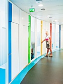 Curved wall with accents of various colours in corridor of contemporary office building