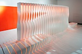 Partition with integrated bench made from shaped blades in front of wall with orange panel