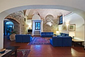 Hotel lobby in historical building with terracotta tiles and modern seating with blue upholstery