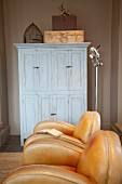 Interior with leather armchairs and simple wooden cupboard