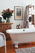 Traditional bathroom with free-standing bathtub, vintage chest of drawers and magnificent bouquet of roses in glass vase