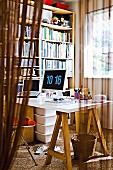 View into the study with a simple, jacked up desk and a large bookshelf