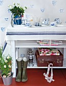 Classic white and blue crockery on shelf and as wallpaper motif; floral fabrics and vintage suitcase