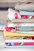 Stacked offcuts of various rose-patterned fabrics