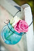 Two roses in blue glass sphere with wire handle hanging from back of chair