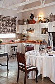 Country-house-style kitchen with antique leather chairs around set table with white tablecloth