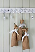 Advent calendar made from small, numbered linen bags hung on wooden rack