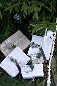 Simply wrapped gifts labelled with Swedish Christmas greetings under fir tree outside