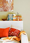 Day bed with pillows and bedspread in orange tones; behind it a white book board