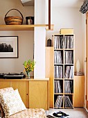 Retro chair in front of fitted sideboard and record collection on modern shelving in corner of living room