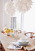Crockery and table decorations on natural-finish wooden table below two designer pendant lamps