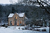 View across snowy stream of caretaker's house belonging to English stately home; twilight scene with lights in windows