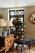 Ottoman upholstered in tartan with antler legs in front of decorated Christmas tree and antique chest of drawers in English living room
