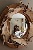 Festively set dining table reflected in mirror with wooden frame decorated with antlers