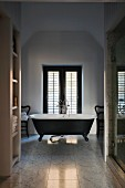 Freestanding, clawfoot, retro bathtub in classic marble bathroom