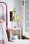 Flowering branch and table lamp on white, retro bedside cabinet next to open, latticed French window