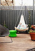 Suspended wicker chair next to planter and other seating on terrace in front of grey screen