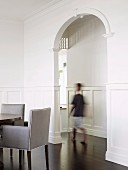 Tall, arched doorway connecting elegant rooms with white wall panelling and exotic wood parquet floor