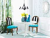 Corner of traditional, elegant living room with blue ceramics and vase of daffodils on white, round wooden table